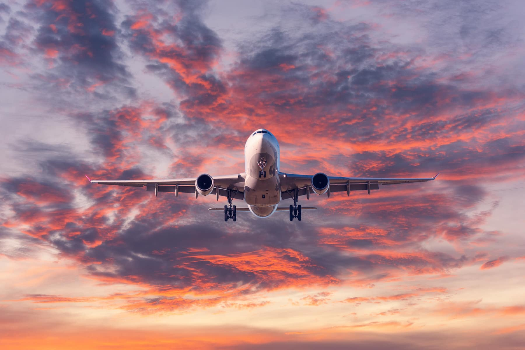 landing-passenger-airplane-at-colorful-sunset-MRSHV6Q